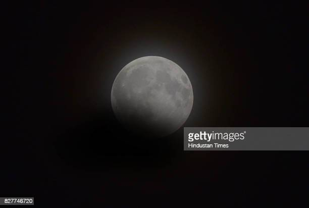 A partial lunar eclipse seen under the cloudy weather the duration time of the eclipse in 5 hours approximately on August 7 2017 in Ludhiana India...