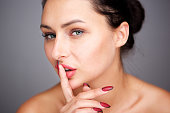partial portrait of mysterious woman with finger pressed to lips