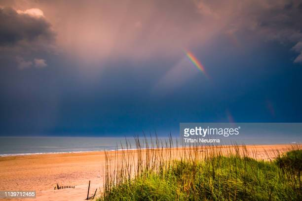 partial rainbow over partial beach dunes with grass and clouds showing - horizontal orientation - north carolina photos et images de collection