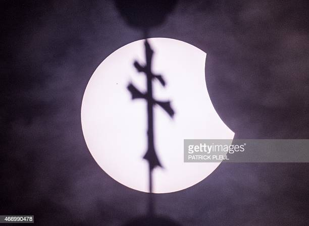 A partial solar eclipse can be seen behind the cross on the spire of Kloster Neuzelle monastery in Neuzelle eastern Germany on March 20 2015 A...