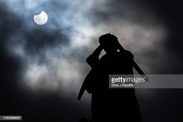 Partial solar eclipse is seen behind the Crimea and Indian Mutiny memorial outside Westminster Abbey on June 10, 2021 in London, England. Viewers in...