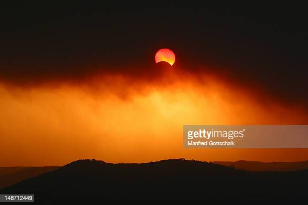 Partial solar eclipse on 04/12/2002 through thick plume of bushfire smoke over Broken Bay.