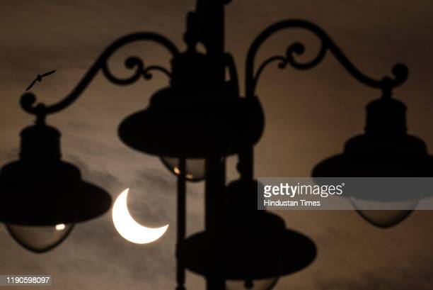 Partial Solar Eclipse seen in the sky from outside the Mumbai CSMT station, on December 26, 2019 in Mumbai, India. A solar eclipse occurs when the...