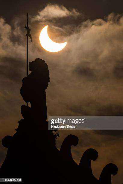 Partial Solar Eclipse seen in the sky over the statues of Mumbai CSMT station, on December 26, 2019 in Mumbai, India. A solar eclipse occurs when the...