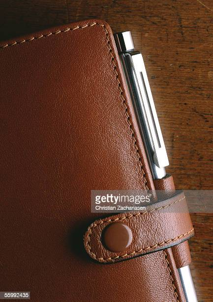 Partial view of brown leather agenda with pen, extreme close-up