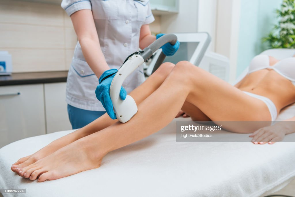 Partial view of cosmetologist in rubber gloves doing laser hair removal procedure on legs : Stock Photo