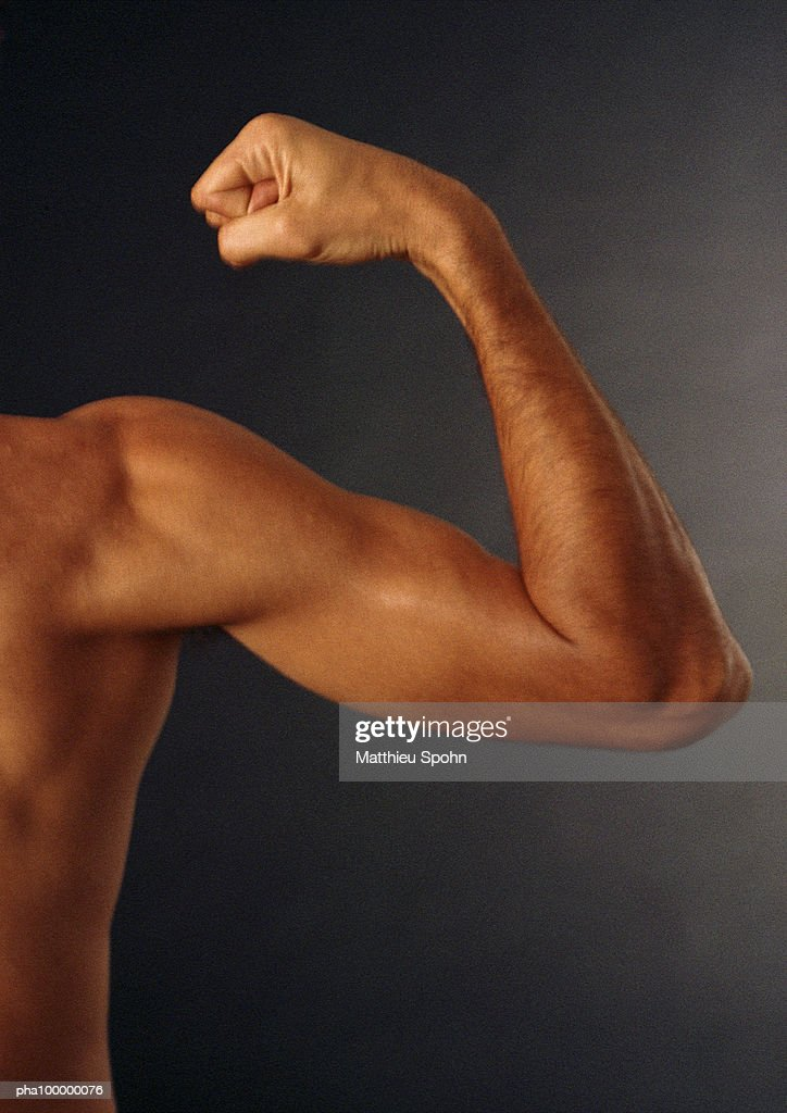 Partial view of nude man's torso, out of frame, bare arm flexed, clenched fist, close-up : Stockfoto