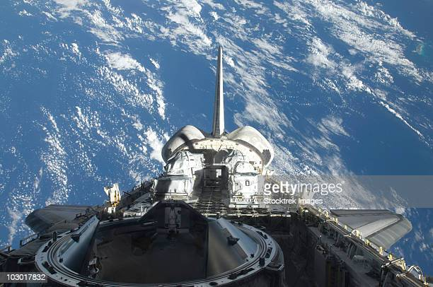 a partial view of space shuttle atlantis backdropped by a blue and white earth. - vertical stabilizer stock pictures, royalty-free photos & images