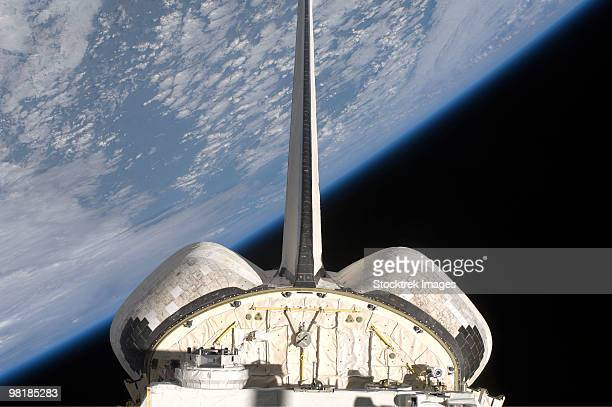 A partial view of Space Shuttle Endeavour backdropped by Earth's horizon.