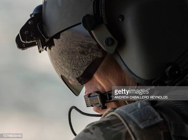 A partial view of the Iraqi capital Baghdad is reflected in the visor of a US Army helicopter crew member as he looks out of a Chinook helicopter...