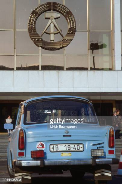 Partial view of the Palace of the Republic with GDR emblem. In the foreground a Trabant car. .