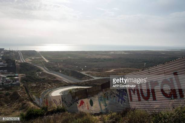 A partial view of the USMexico border wall painted by members of the Brotherhood Mural organization is pictured in Tijuana Mexico on July 6 2017 US...