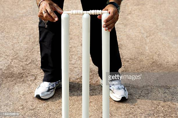 Partial view of umpire adjusting bails on wickets