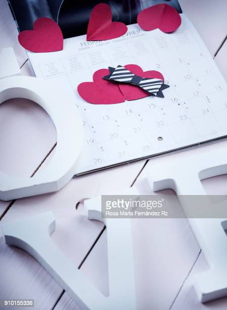 Partial view of white wooden letters of the word love, calendar sheet with paper hearts shape and bow tie pointing Valentine's day.