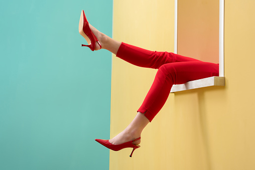 partial view of woman in red pants and shoes outstretching legs out decorative window 971618048