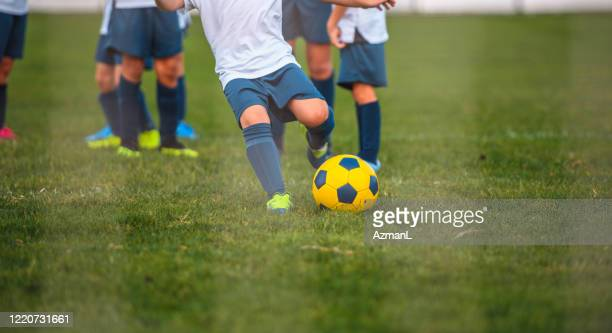 partial view of young boy footballer practicing goal kick - sports training camp stock pictures, royalty-free photos & images