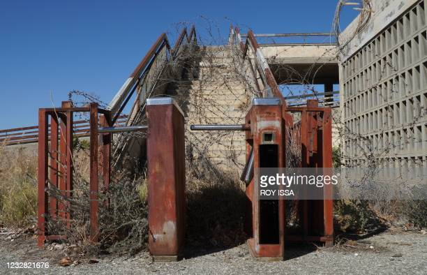 Partial view shows a rusted turnstile and barbed wire around the abandoned building of Nicosia's former airport in the UN-protected buffer zone of...