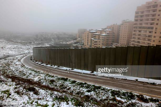Partial view shows Israel's controversial separation wall and the Palestinian Shuafat refugee camp following heavy snowfall in the Israeli-annexed...