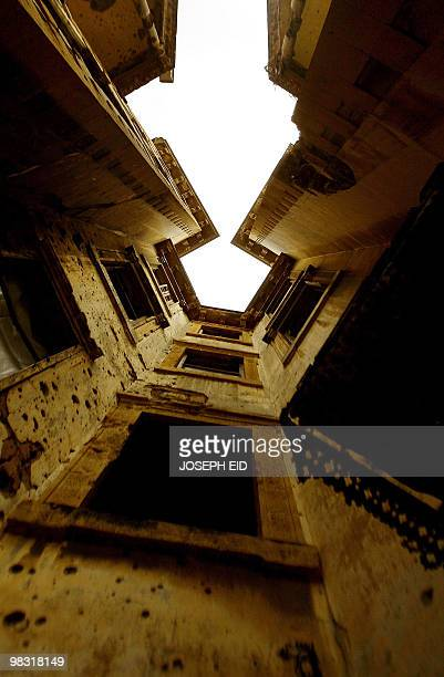 A partial view shows the bulletriddled walls of a warravaged building at Sodeco Square in the Lebanese capital Beirut on April 7 2010 With sandbags...