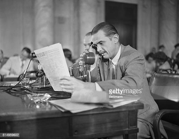 Partially deaf plane builder Howard Hughes shown using a special hearing aid provided by the Senate War Investigating Committee now probing his war...