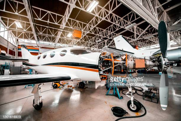 partially disassembled small propeller airplane with opened motor compartment in a maintenance hangar - fuselage stock pictures, royalty-free photos & images
