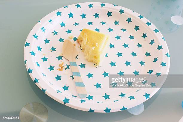Partially eaten piece of cake on festive paper plate