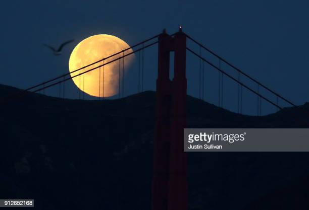 A partially eclipsed super blue blood moon sets behind the Golden Gate Bridge on January 31 2018 in San Francisco California The 'super blue blood...