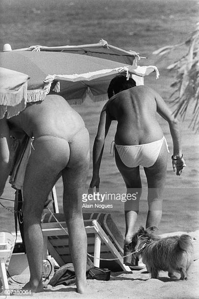 A partially nude couple sunbathes on a StTropez Beach The man on the left wears a gstring and the woman at right is wearing bikini briefs