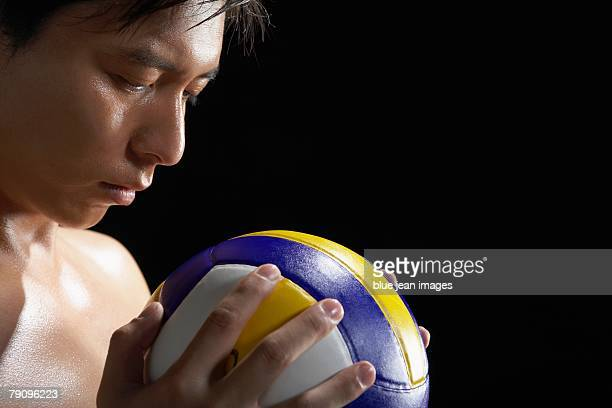A partially nude man holding a volleyball and staring it.