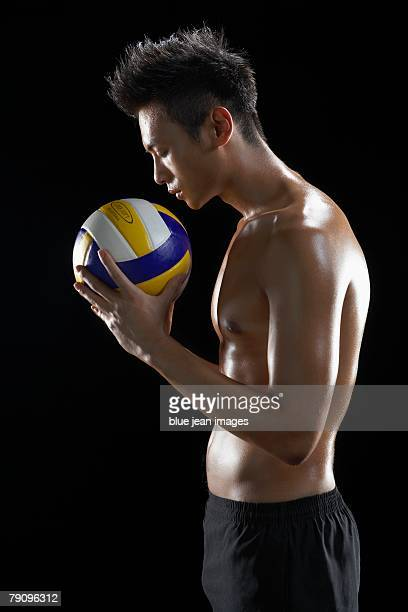 A partially nude man holding a volleyball.