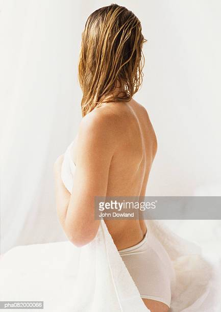 partially nude woman sitting head turned away, side view. - female bare bottoms stock photos and pictures