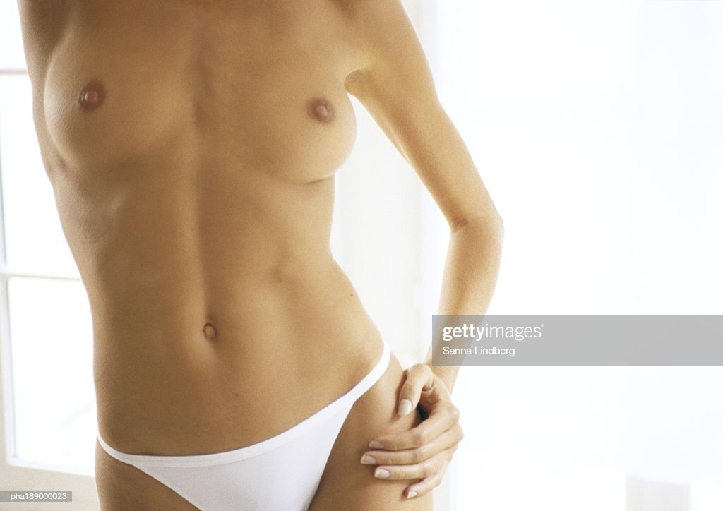Partially nude woman standing with hand on hip, mid section, close-up. : Stockfoto