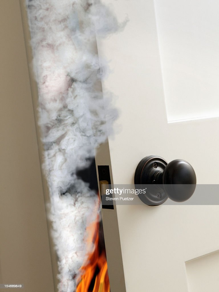 Partially open door with smoke and fire behind it & Smoke Door Stock Photos and Pictures   Getty Images