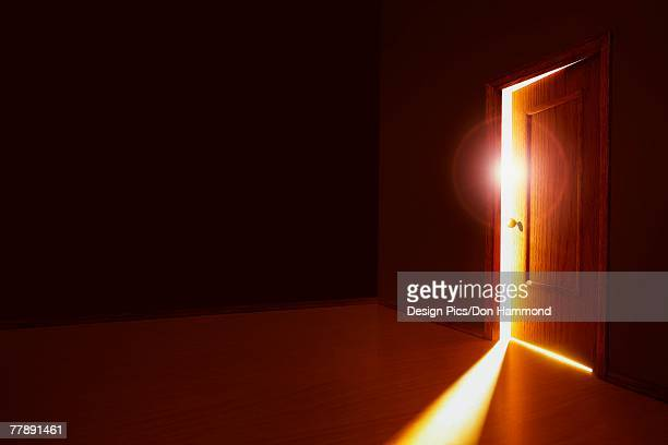 partially opened door with bright light - magic doors stock pictures, royalty-free photos & images