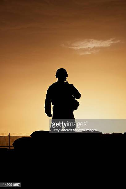 partially silhouetted u.s. marine on a bunker in northern afghanistan. - afghanistan stock pictures, royalty-free photos & images
