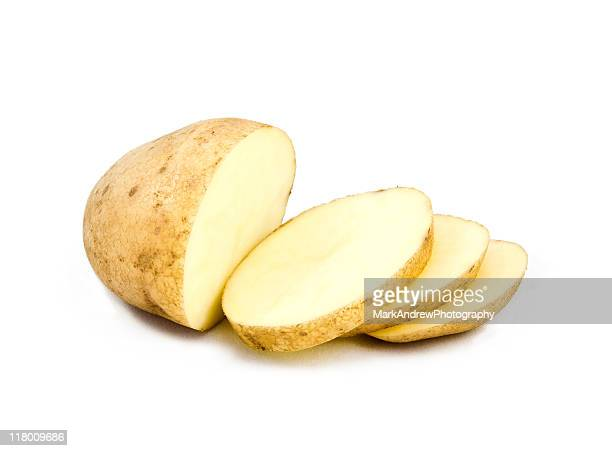 a partially sliced potato on white - rauwe aardappel stockfoto's en -beelden