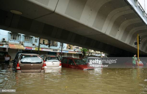 Partially submerged cars are seen along a flooded road during heavy rain showers in Mumbai on August 29 2017 Heavy rain brought India's financial...