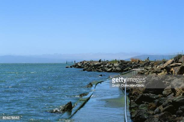 Partially submerged footpath near the waters of the San Francisco Bay with people fishing nearby at Crown Memorial State Beach an East Bay Regional...