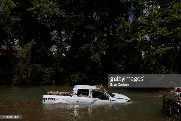 Partially submerged Ford F-150 sits in Trace Creek on August 23, 2021 in Waverly, Tennessee. Heavy rains on Sunday caused flash flooding in the area,...
