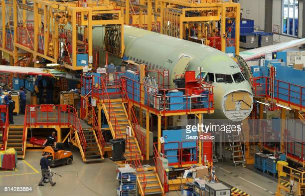A partiallyfinished passenger plane of the A320 series stands in an assembly hall at the Airbus factory on July 14 2017 in Hamburg Germany Both...
