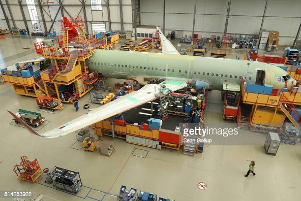 Partially-finished passenger plane of the A320 series stands in an assembly hall at the Airbus factory on July 14, 2017 in Hamburg, Germany. Both...