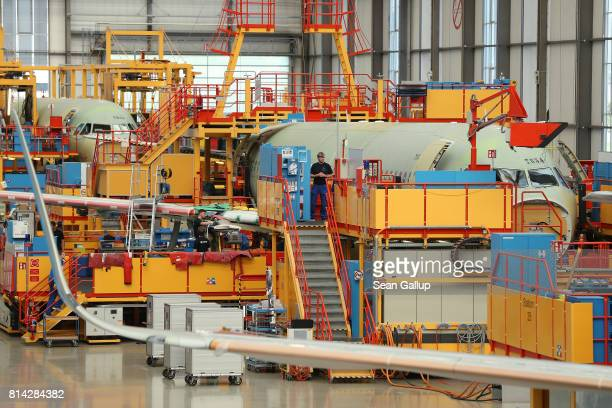 Partiallyfinished passenger planes of the A320 series stand in an assembly hall at the Airbus factory on July 14 2017 in Hamburg Germany Both Boeing...