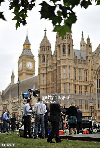 Partially-sighted man walks past as television news crews report from the outside the Houses of Parliament in central London on June 3, 2009. British...