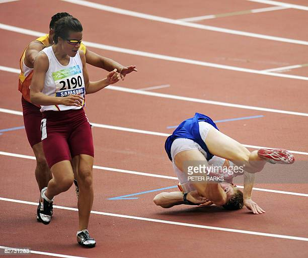 Partially-sighted runner Irene Suarez of Venezuela avoids the guide of runner Tracy Hinton of Britain as he falls at the finish of the 100m T11 final...
