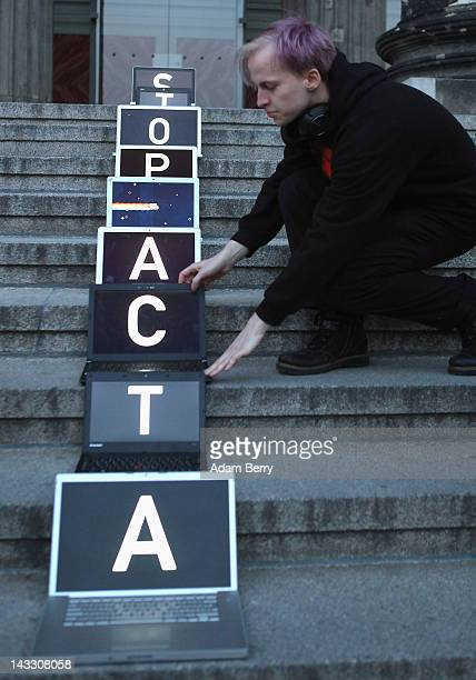 A participant arranges laptop computers featuring screens with letters spelling out the words 'Stop ACTA' during a demonstration against Internet...