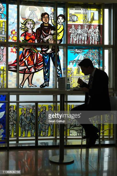 A participant at the Global Solutions Summit eats next to a communistera stained glass Socialist Realist mural by artist Walter Womacka at the...