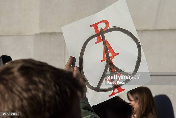 A participant at the mass vigil in Washington Square Park holds aloft a sign reading 'Peace' superimposed over a modified peace emblem illustrated...