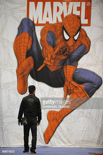A participant at the New York ComicCon 2009 the city's main comic books fair walks past a giant Spiderman poster in New York on February 6 2009 The...