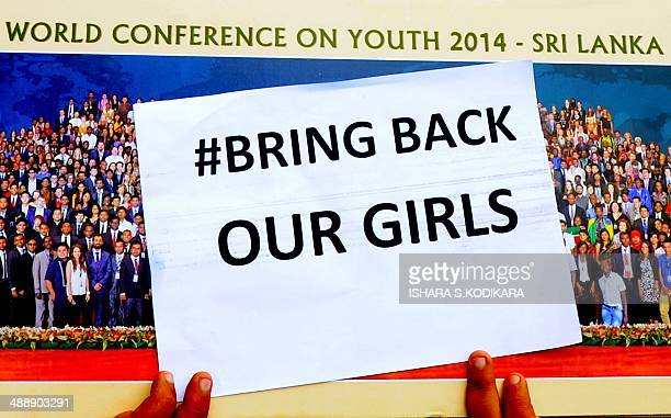A participant at the World Conference on Youth 2014 hosted by Sri Lanka poses for a photograph while holding a placard during a protest to demand the...