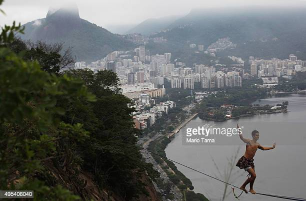 A participant balances on a slackline set up between rocks in the Cantagalo favela community during the Highgirls Brasil festival on November 2 2015...